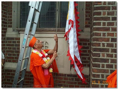 HDH Acharya Swamishree performing the flag ceremony