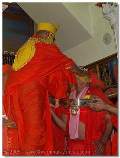 HDH Acharya Swamishree applies chandan prasad on a sant