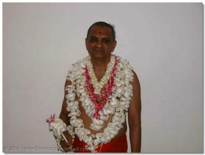 HDH Acharya Swamishree gives His divine darshan adorned in flower garlands, bracelets and anklets