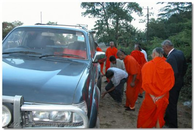 Acharya Swamishree examining the vehicle after a puncture