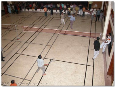Devotees play badminton during the indoor sports tournament