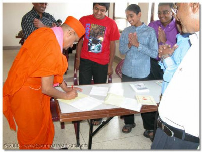Acharya Swamishree signs and blesses the students' excercise books