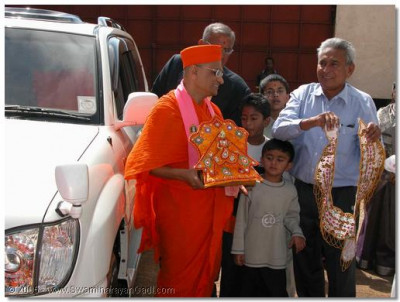 Acharya Swamishree arrives at the factory of one of the Ugandan devotees