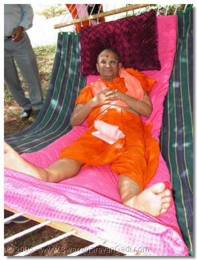 His Divine Holiness Acharya Swamishree gives gives His divine darshan swaying from a hammock