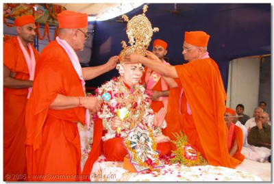 HDH Acharya Swamishree places a gold moughat on HDH Jeevanpran Swamibapa's head