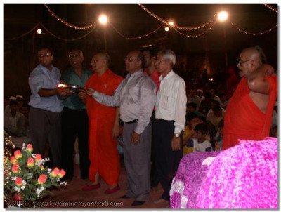 HDH Acharya Swamishree and devotees doing aarti to Lord SwaminarayanBapa Swamibapa