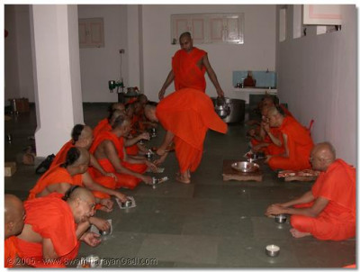 HDH Acharya Swamishree and sants having prasad of 'doodh pova' and 'gotas'