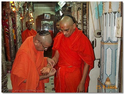 Sadguru Shree Bhaktavatsaldasji Swami putting a rakhadi on HDH Acharya Swamishree in August 1999
