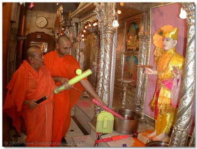 Sadguru Shree Bhaktavatsaldasji Swami showering Lord Swaminarayan with coloured water during the fooldolotsav celebrations