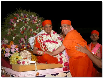 Sadguru Shree Bhaktavatsaldasji Swami putting a garland on HDH Acharya Swamishree