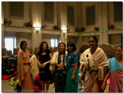 The UN Ambassador's wife being presented with a prasadi shawl.