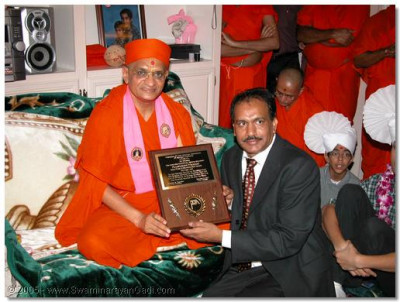 Shree Prashantbhai presents a commendation plaque to HDH Acharya Swamishree