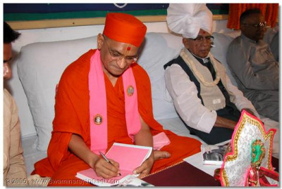 HDH Acharya Swamishree signing copies of the book