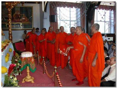 Acharya Swamishree and sants performing aarti to Lord Swaminarayanbapa Swamibapa during the poojan ceremony