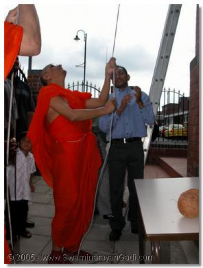 Acharya Swamishree raising a ceremonial flag during the patatsov festivities