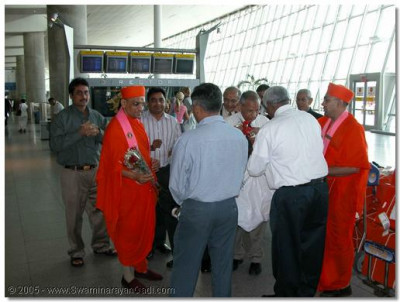 Acharya Swamishre is greeted by devotees at New York's John F Kennedy International Airport