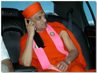Whlie Acharya Swamishree is driven in a limosine to an awaiting helicopter, He phones devotees around the world to let them know that He has arrived safely in the USA