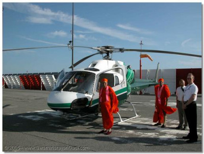 Acharya Swamishre gives darshan next to the helicopter