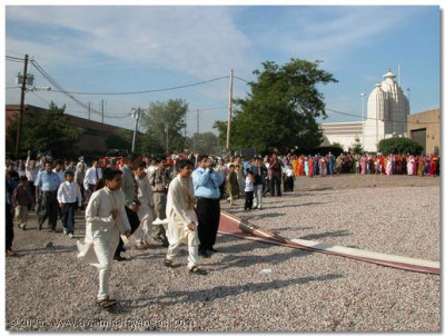 Gathered devotees rejoice at the arrival of Acharya Swamishree