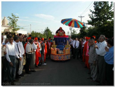 Acharya Swamishree is taken towards the temple entrance on a beautifully decorated float
