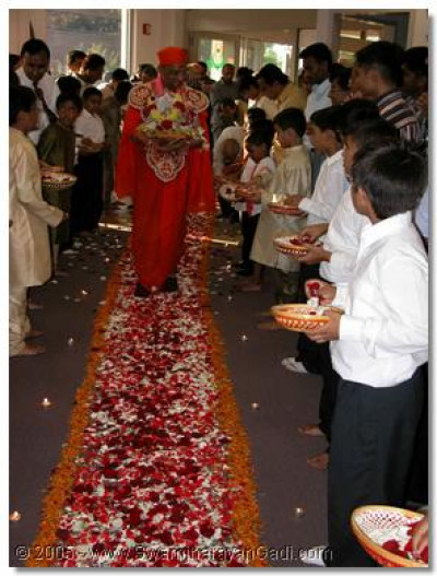 Young devotee greet Acharya Swamishree with flowers