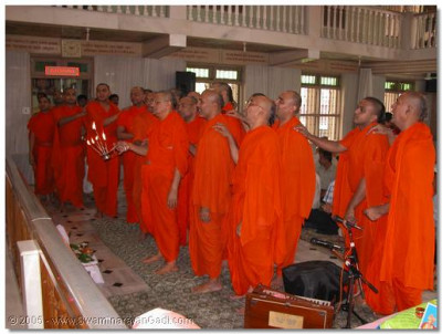 Acharya Swamishree and the sants perform aarti to the Lord