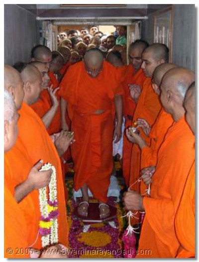 Acharya Swamishree accepts the wishes of His beloved sants and places silver Chakra (ornate sandals) on His feet