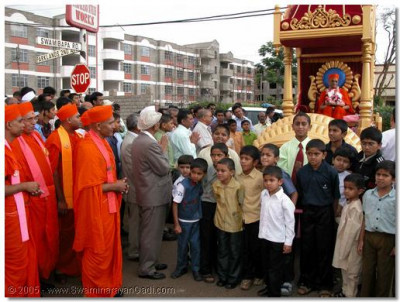 Acharya Swamishree gives darshan seated on a chariot drawn by young children