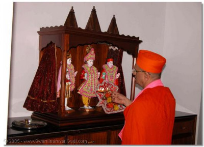 Acharya Swamishree performs aarti to the Lord who presides in the Temple in Uganda