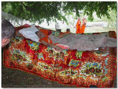 Acharya Swamishree rests in a hammock, under the shade of a tree