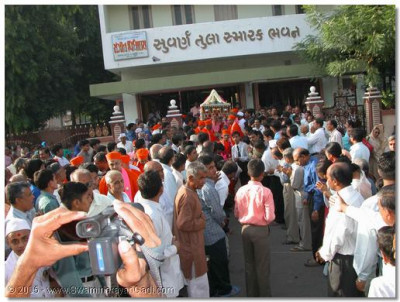 Acharya Swamishree leads a procession from Shree Swaminarayan Tower to Sabha Mandap, during which Jeevanpran Swamibapa's Sants carry their beloved Gurudev in the ornately decorated palanquin