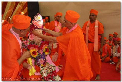 Acharya Swamishree adorns Jeevanpran Swamibapa with a moogat decorated with fresh flowers
