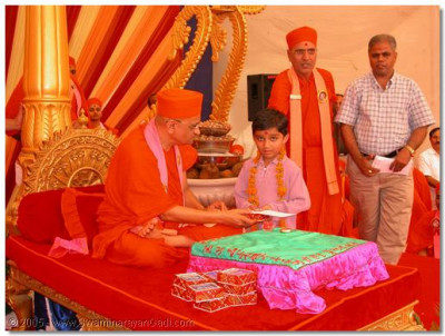 His Divine Holiness Acharya Swamishree gives darshan to and commends the highest educational achievers of the Chatralay
