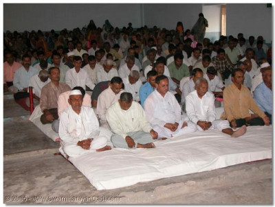 Devotees in the assembly perform meditation