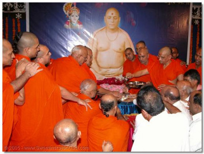 Acharya Swamishree, sants and devotees perform panchamrut abhishek (ceremonial bathing with the five nectars) to the divine lotus feet of Jeevanpran Swamibapa