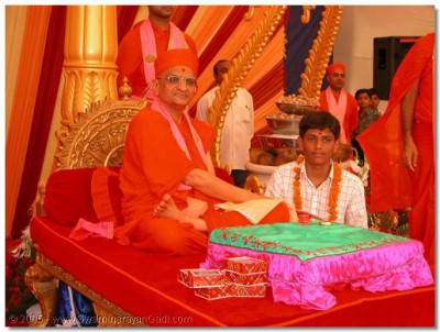 His Divine Holiness Acharya Swamishree gives darshan to a devotee who won the Gujarat Karate Championships