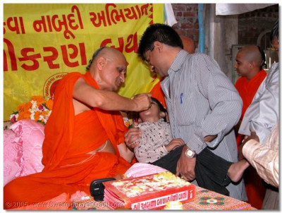 Acharya Swamishree giving the polio vaccine drops to young children