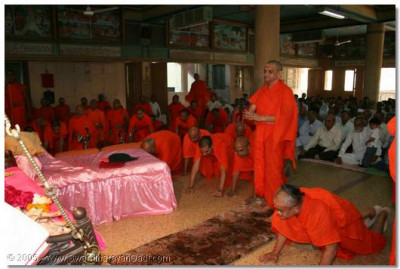 Acharya Swamishree and sants perform prostrations to the Lord