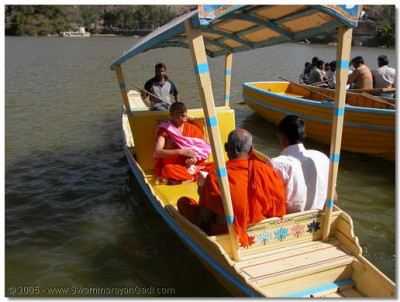 Acharya Swamishree gives darshan seated in a boat