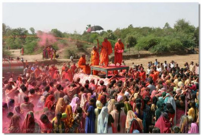 Acharya Swamishree blesses the crowd by spraying them all with coloured prasadi water