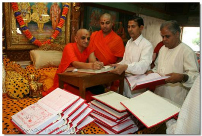 Businessmen present their account books for the New Year to Acharya Swamishree to sign and sanctify