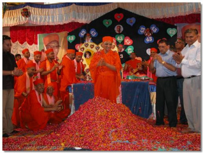 Acharya Swamishree is engulfed in flower petals