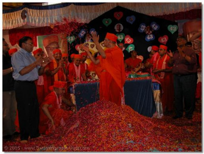 Acharya Swamishree graces sants and devotees with prasad flower petals