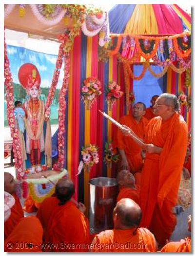 Acharya Swamishree squirting coloured water on Lord Swaminarayan