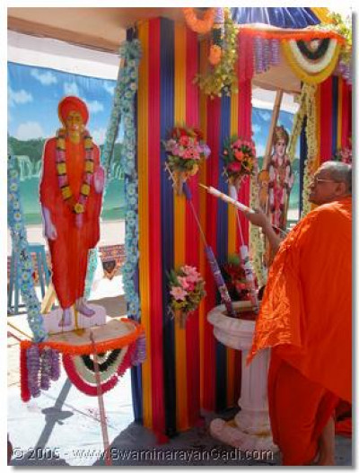Acharya Swamishree squirting coloured water on Sadguru Shree Ishwarcharandasji Swamibapa
