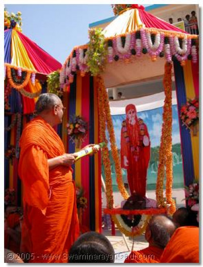 Acharya Swamishree squirting coloured water on Sadguru Shree Gopalanand Swamibapa