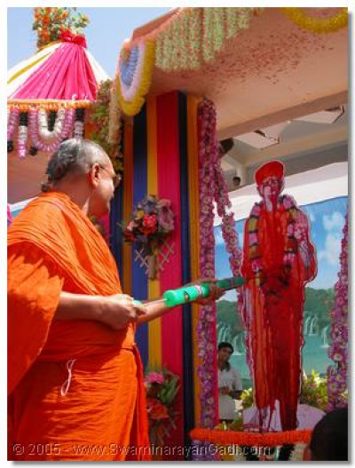 Acharya Swamishree squirting coloured water on Sadguru Shree Nirgundasji Swamibapa
