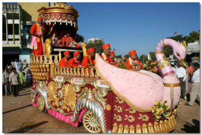Acharya Swamishree and sants give darshan from the chariot, during the welcoming procession