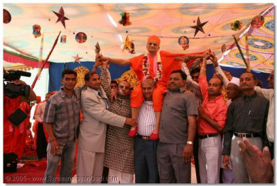 Disciples lovingly carry Acharya Swamishree onto the stage