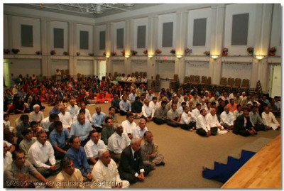 Devotees listen intently to Acharya Swamishree's aashirwad